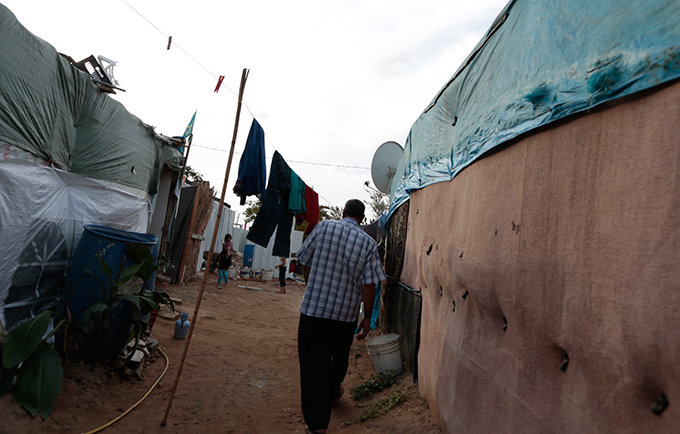 """A community leader makes his way to the tent of a pregnant 14-year-old former child bride. """"I am worried about the delivery,"""" said the girl's father. © UNFPA/David Brunett"""